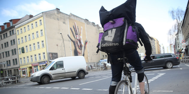 BERLIN, GERMANY - MARCH 09:  A man riding a bicycle for food delivery service Deliveroo pauses at an intersection on March 9, 2018 in Berlin, Germany. A variety of food delivery setvices, including Lieferando, Deliveroo, Foodora and others, have established themselves across Germany. All depend heavily on part-time workers who receive little to no benifits. Some riders have sought to organize themselves into works councils, efforts that have so far failed or been thwarted by the companies.  (Photo by Sean Gallup/Getty Images)