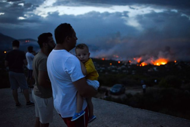 A man holds his son as a wildfire burns in the town of Rafina, near Athens, July 23, 2018.   / AFP PHOTO / ANGELOS TZORTZINIS